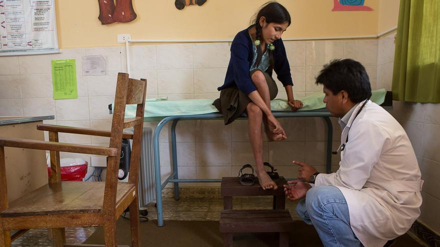 Nelida Llaveta tiene once años. En la foto, le explica al médico que desde hace unos días no puede caminar debido a un intenso dolor de rodillas. En Bolivia, la cobertura sanitaria es solo para menores de cinco años. El seguro de salud estudiantil garantiza la atención a todos los niños y niñas de 5 a 19 años de la comunidad de Sopachuy. (Salva Campillo/AEA).