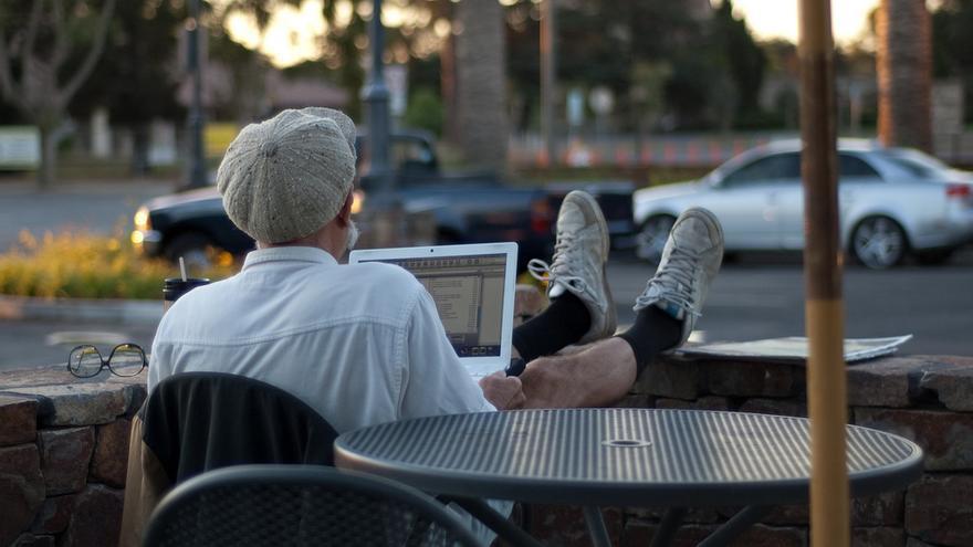Hombre descansa con un portátil en sus piernas