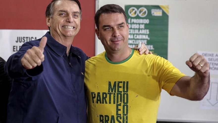 Bolsonaro saluda a las cámaras junto a su hijo Flavio tras votar el domingo.