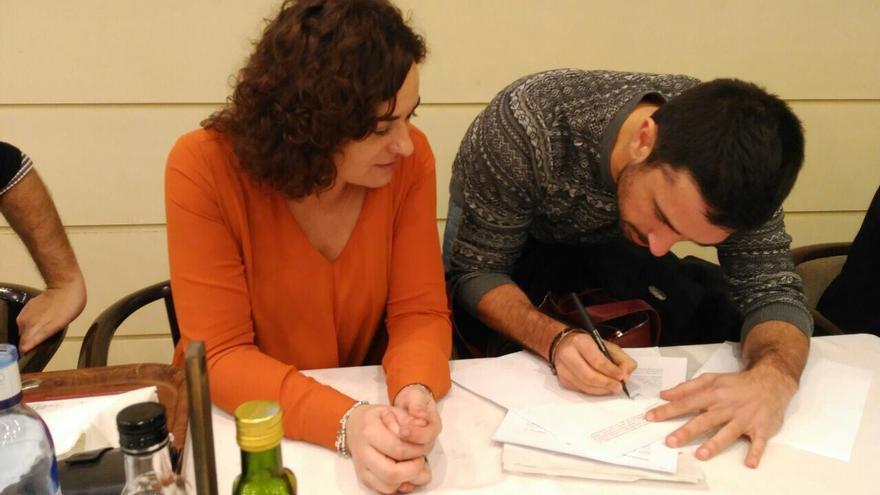 Los senadores Ramón Espinar y Sara Vilá, firmando el acuerdo Podemos - En Comú para el Senado en el comedor