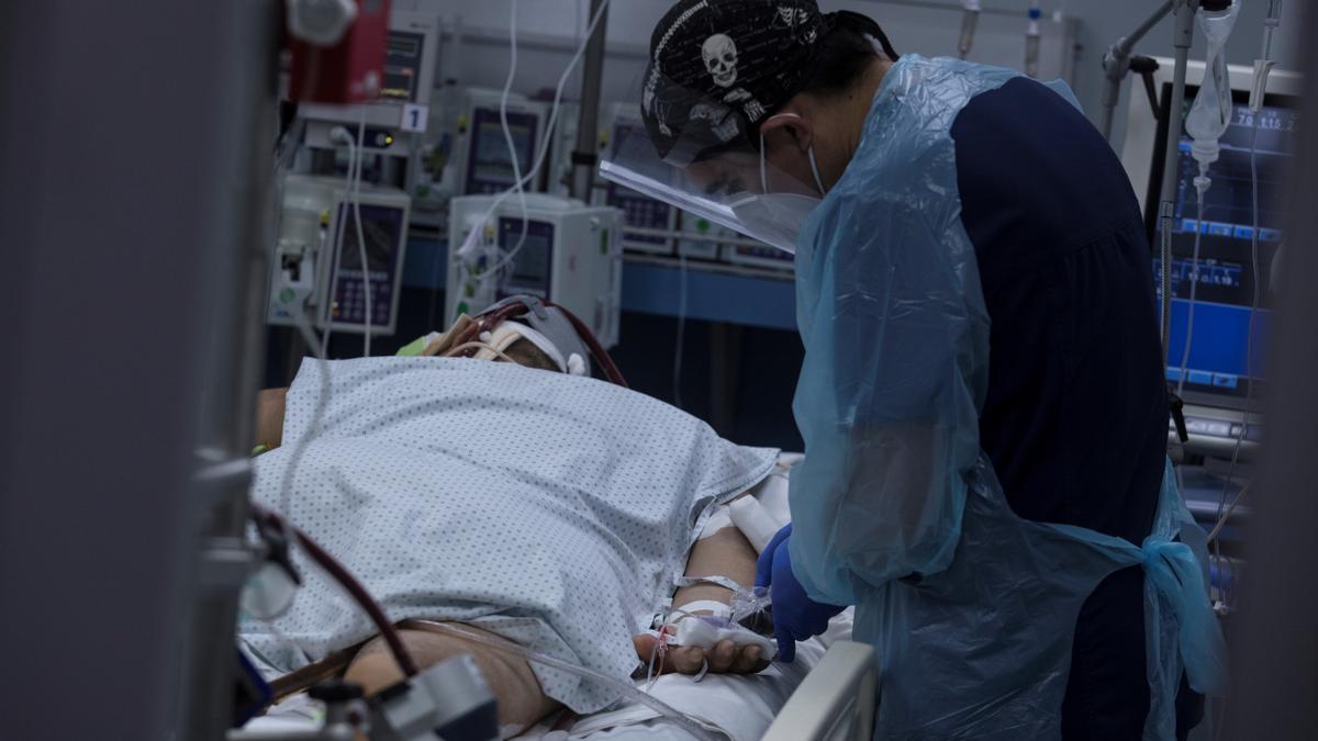 Un sanitario revisa el estado de un paciente con COVID en la UCI de un hospital