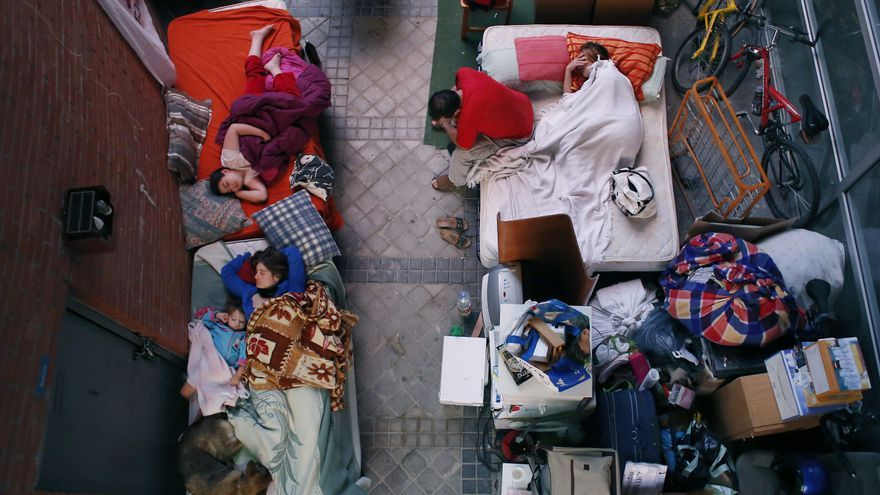 Una familia desahuciada en España durmiendo en la puerta de su casa. / Andrés Kudacki