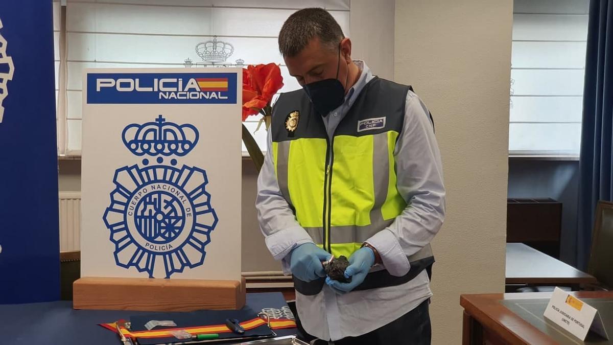 Un agente de la Policía Nacional, con uno de los trozos de carbón en que se ocultaba la cocaína