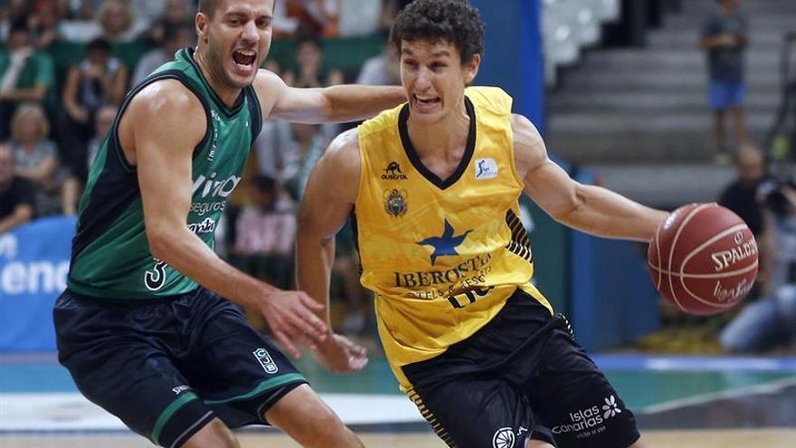 El base del Iberostar Tenerife, Rodrigo San Miguel, intenta avanzar con la pelota, ante la presencia de Albert Sàbat, del Divina Seguros Joventut. EFE/Andreu Dalmau