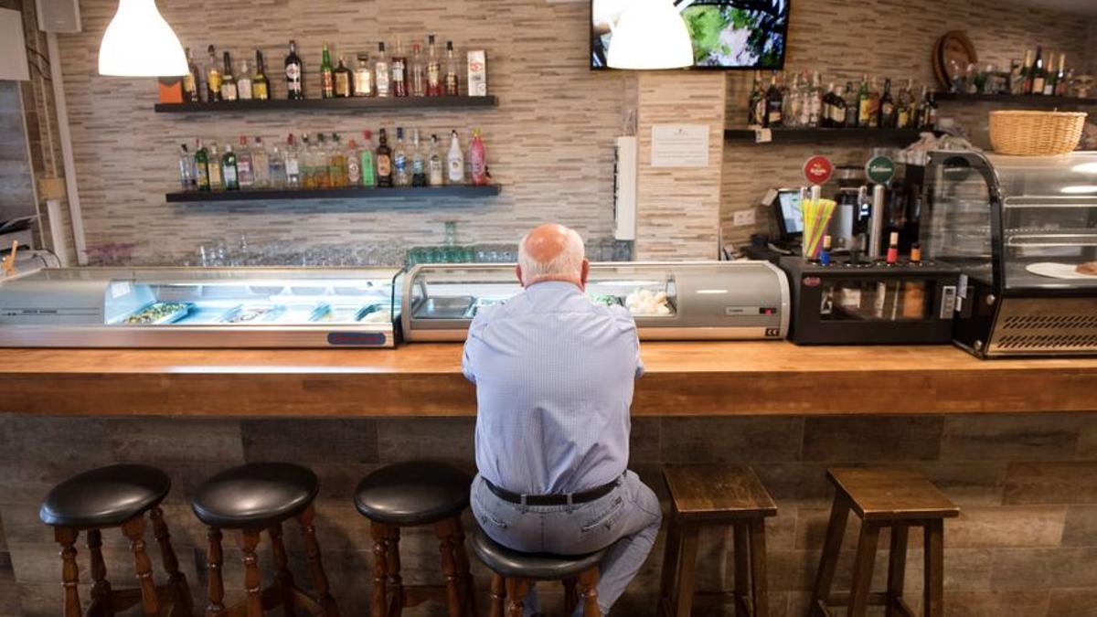 Un hombre espera frente a una barra de bar
