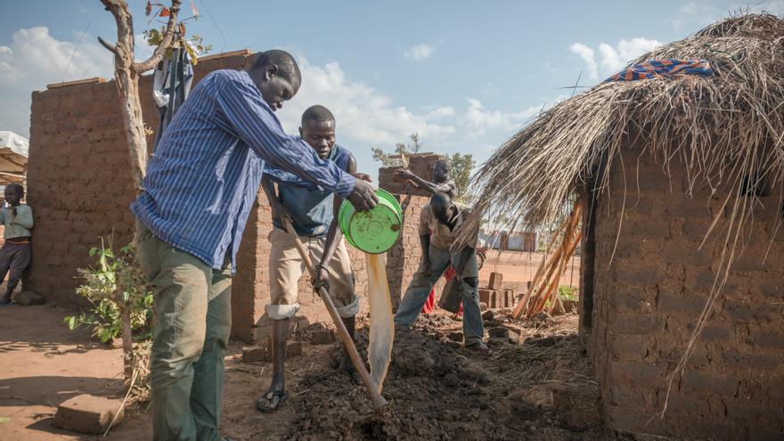 Los refugiados han comenzado a construir cabañas tradicionales de barro para reemplazar los refugios temporales hechos con láminas de plástico. Muchos creen que tendrán que permanecer allí durante años. Finalmente, los asentamientos de refugiados y las aldeas han comenzado a proliferar en la que era una región relativamente deshabitada del norte de Uganda. Fotografía: Yann Libessart/MSF