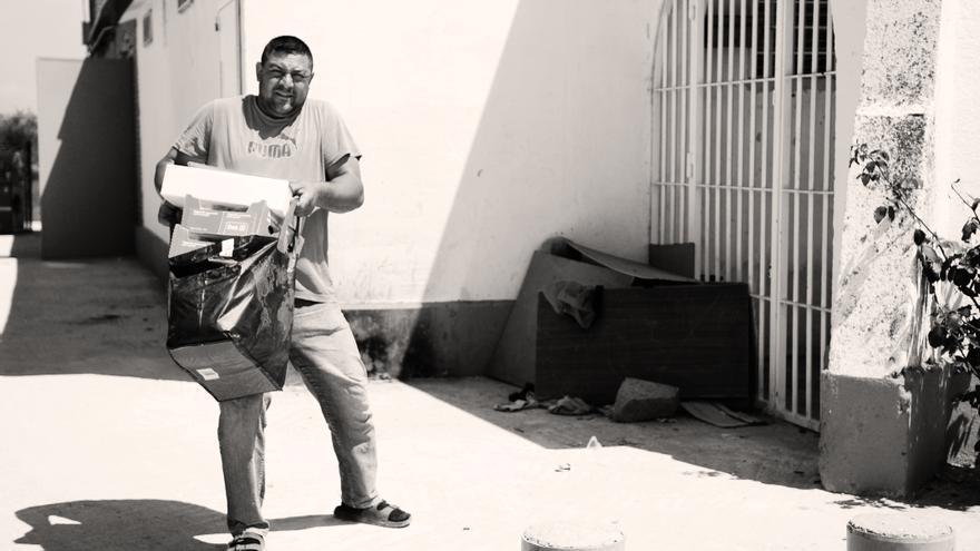 Un ciudadano del asentamiento del Gallinero recoge su bolsa de comida del banco de alimentos en la parroquia