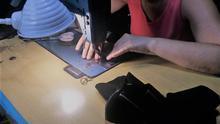 Una aparadora trabaja con una máquina de coser