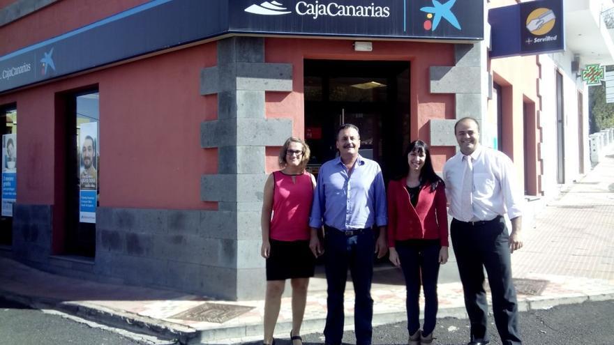 En la imagen, el alcalde y la concejal de Servicios Sociales, junto a representantes de La Caixa, delante la sucursal de la entidad en el municipio.