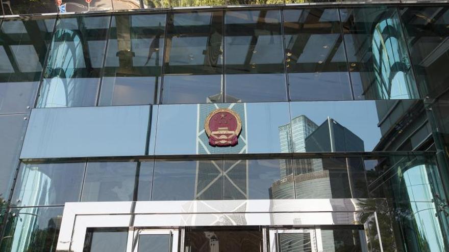 El sello del gobierno chino se ve frente a un reflejo del Banco de China.