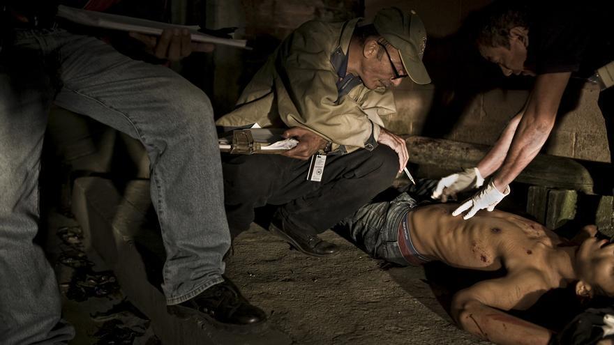 El doctor Abullarade inspecciona las heridas de bala de un cadáver. A Abullarade le cuesta recordar un día de trabajo sin tener que acudir a una escena de homicidios en los últimos años. El Salvador, el menos de los países de América tuvo más de 4 mil homicidios en 2011./Edu Ponces (RUIDO Photo)