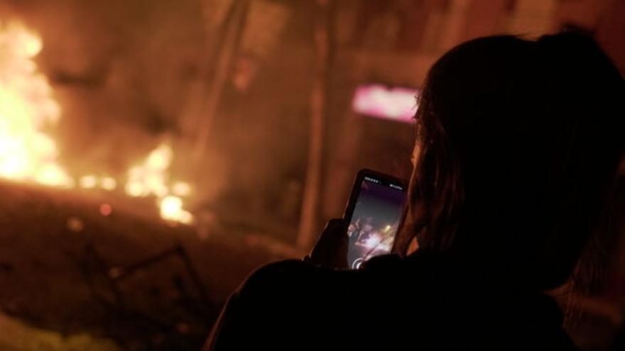 Una joven documenta con su teléfono móvil el fragor de una situación de violencia callejera.
