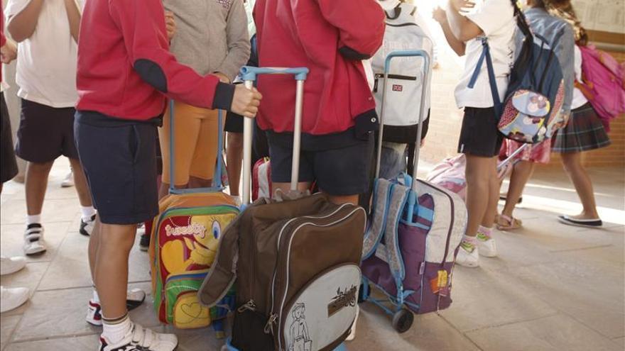 Varios alumnos llegan con sus mochilas al colegio.