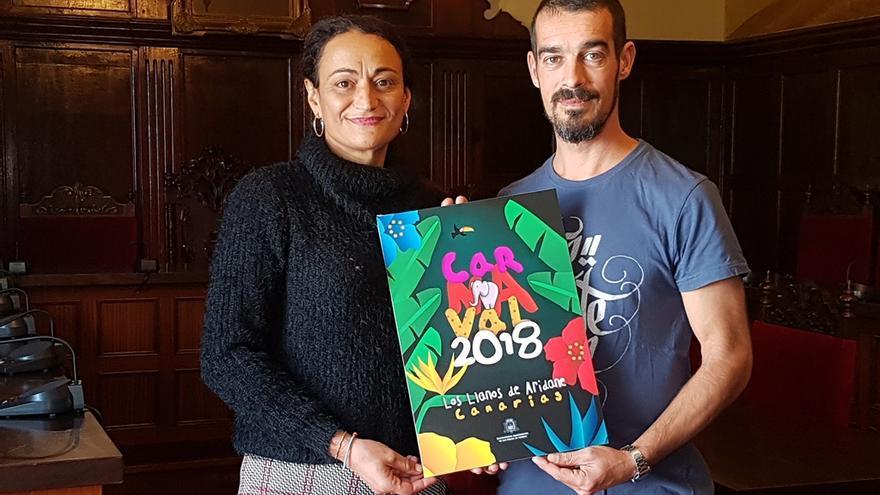 El ganador del concurso muestra el cartel del Carnaval aridanense junto a la concejal de Fiestas.