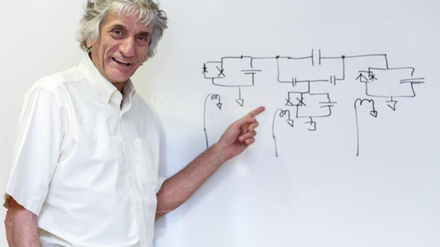 John Martinis posa en el ICMAT delante de un esquema de circuitos dibujado por él mismo.
