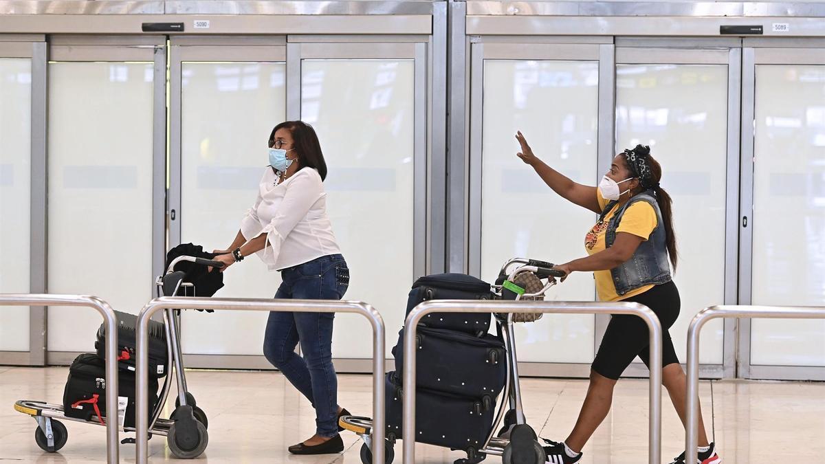 Dos turistas caminan por la T4 de Barajas este lunes, cuando España ha autorizado la entrada de viajeros con la pauta completa de la vacuna contra la COVID-19