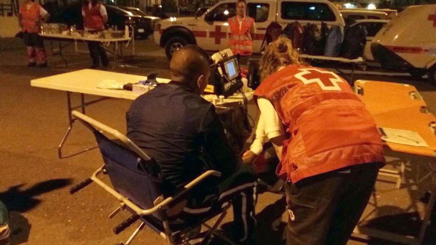 Miembros de la Cruz Roja atienden a un grupo de inmigrantes en Alicante