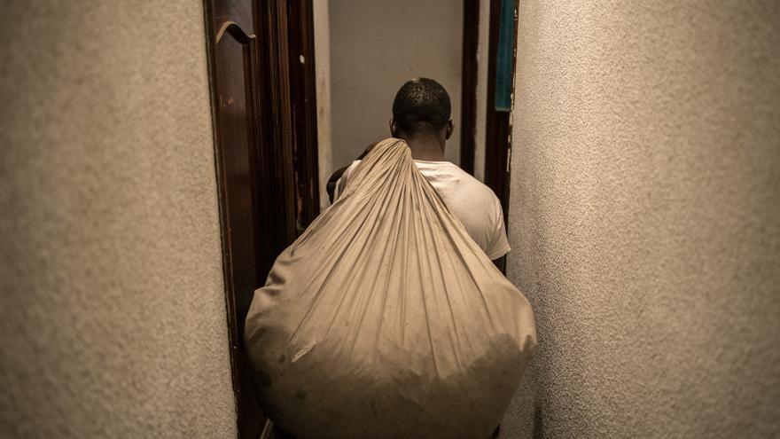 Serigne traslada una manta cargada de camisetas al recibidor de su casa.
