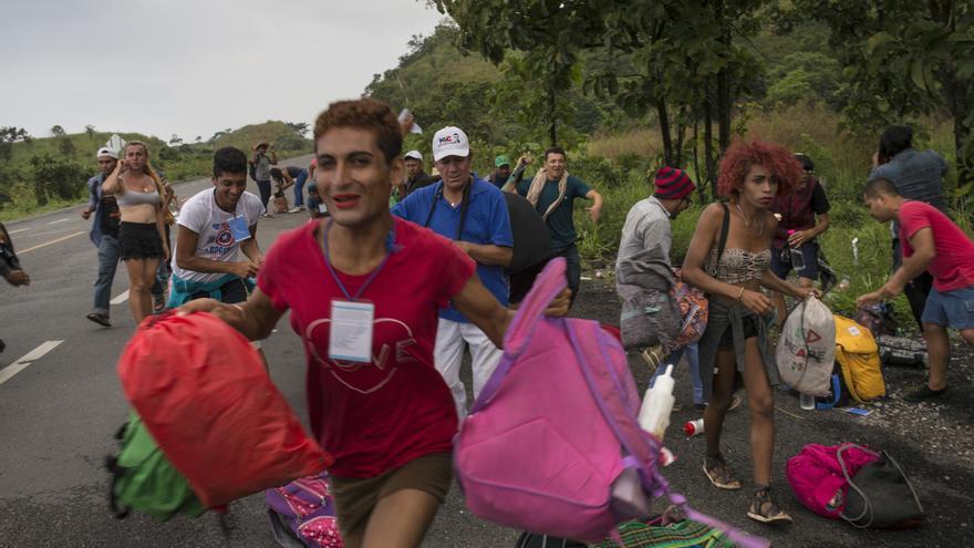 Integrantes de un grupo de personas LGBTQ que viajan con la caravana de migrantes centroamericanos corren hacia un camión que se detuvo para llevarlos, en el camino a Sayula, México. Gran parte de la caminata se ha hecho a pie, pero los viajes en autoestop han sido cruciales, especialmente en los días en que viajan 100 millas o más. Para el grupo LGBTQ, ha sido más difícil hacerlo.Foto: AP/Rodrigo Abd