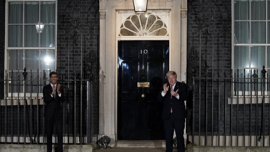 Boris Johnson y el ministro de Hacienda, Rishi Sunak, aplauden al personal sanitario en la entrada del 10 de Downing Street el 26 de marzo.