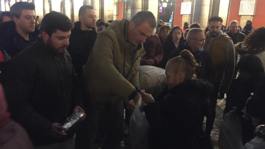 El secretario general de Vox, Javier Ortega Smith, repartiendo comida a las personas sin hogar en la Plaza Mayor.