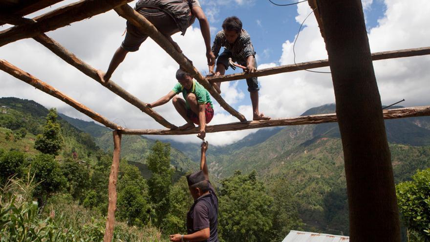 Un grupo de vecinos ayudan a construir un refugio temporal en Gyalthum (ActionAid)