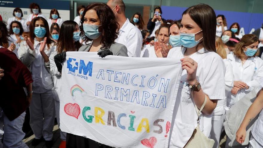 La presidenta de la Comunidad de Madrid, Isabel Díaz Ayuso (i), sostiene una pancarta junto una sanitaria durante el acto de cierre del hospital de campaña del recinto ferial de Ifema este viernes.