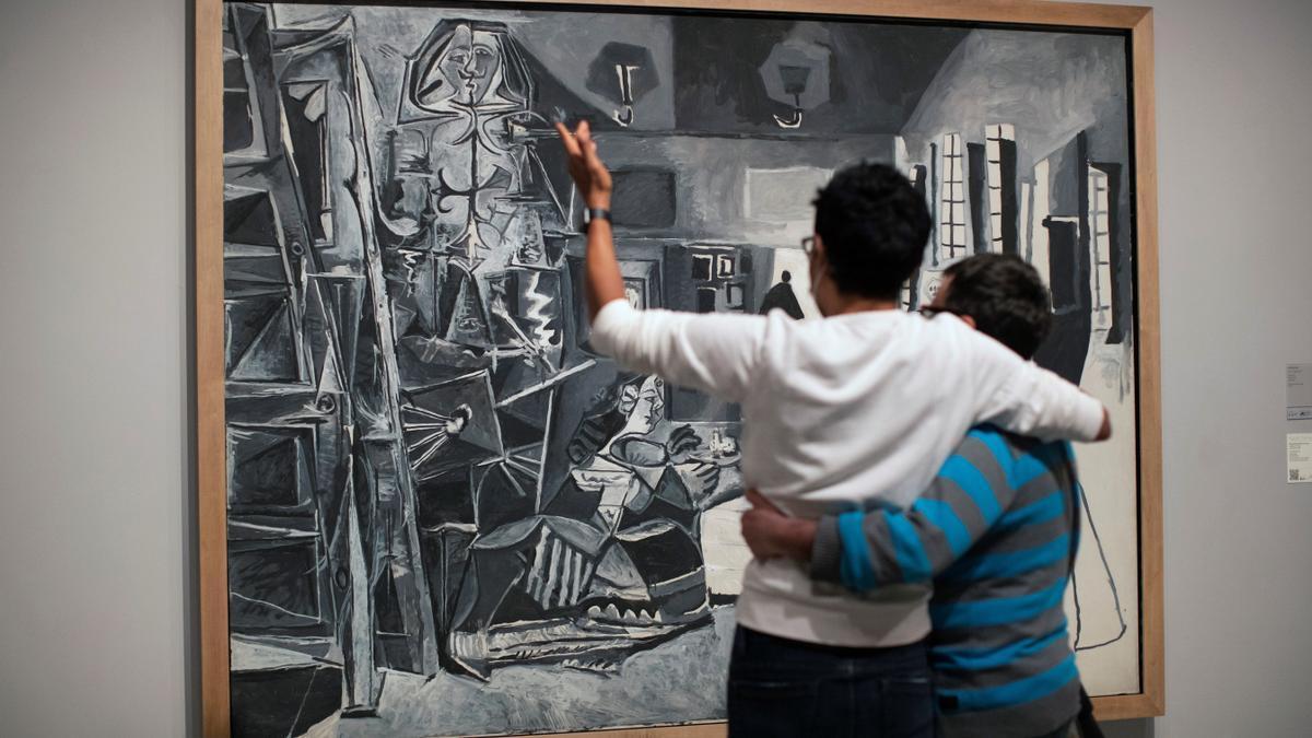 Una pareja observa 'Las Meninas' en una sala del Museo Picasso