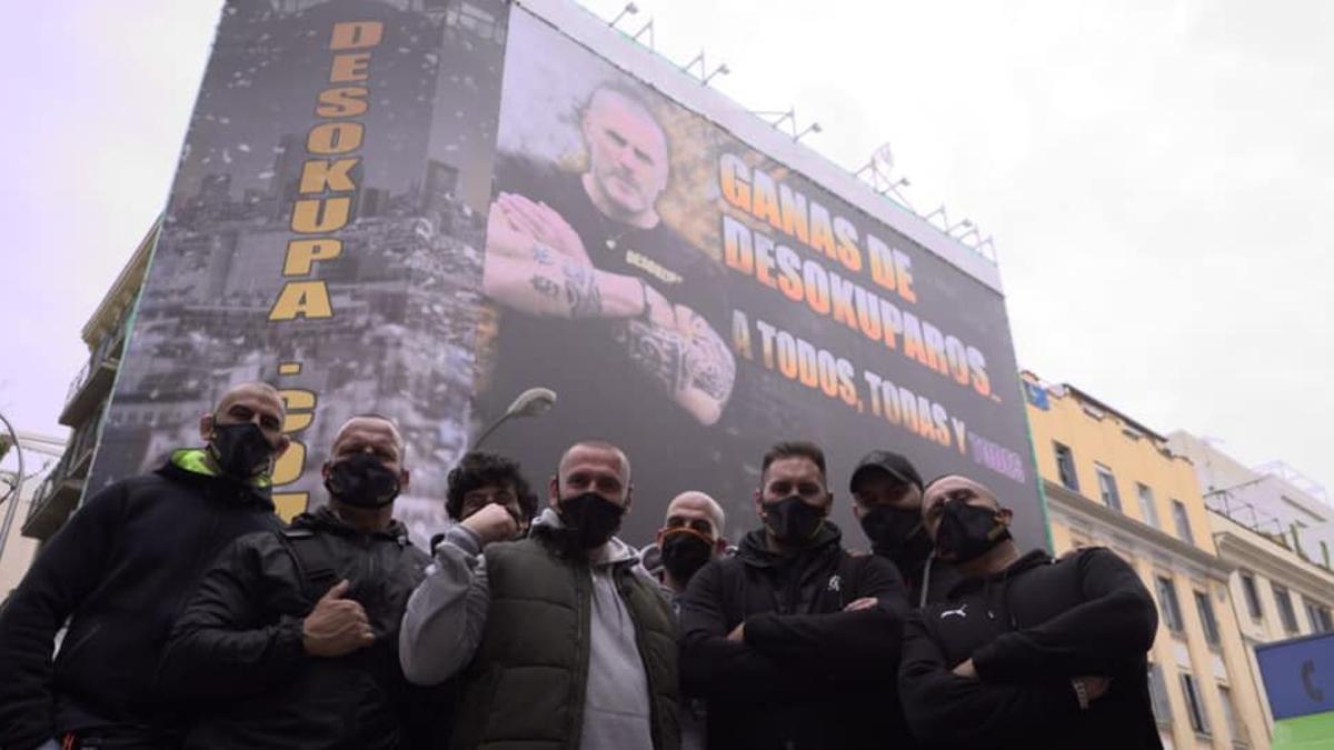 """Miembros de la empresa de ultras Desokupa frente a un cartel anunciando """"sus servicios"""""""