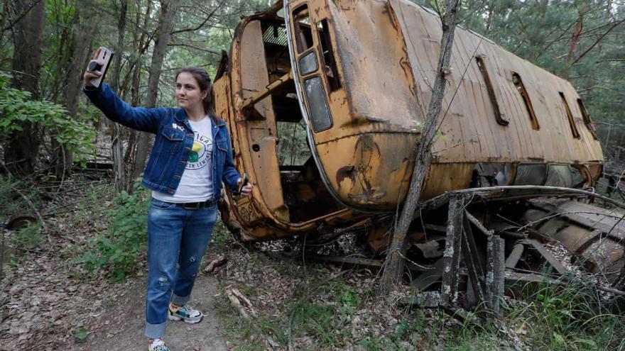 Una visitante toma una fotografía delante de un autobús abandonado durante un tour a Chernóbil. Fotografía de Sergey Dolzhenko/EPA