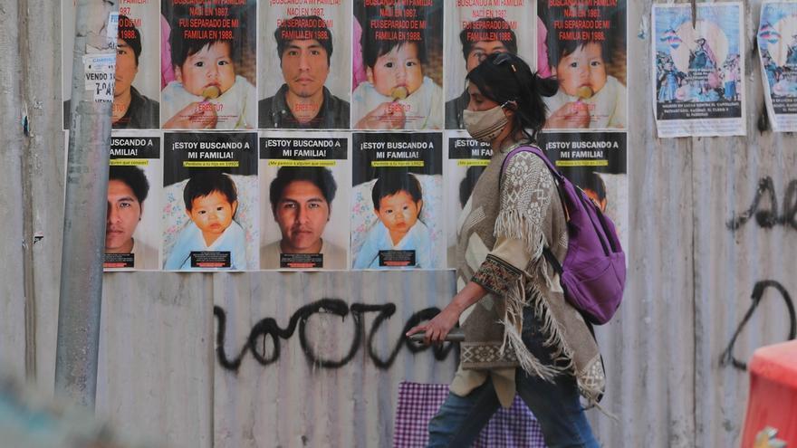 Imagen del 30 de junio de 2020 de una mujer que pasa junto a carteles con los rostros de Atamhi y Vicente, dos jóvenes que buscan a sus familias biológicas en La Paz (Bolivia).