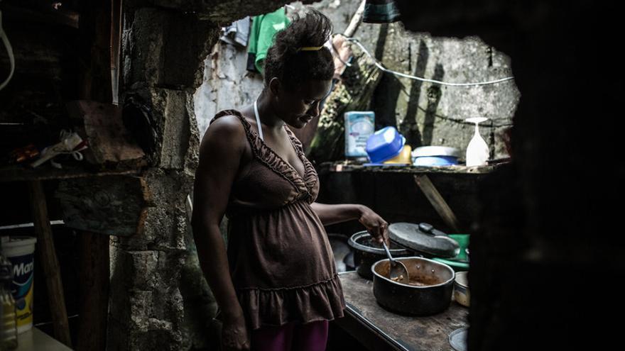 """Rosa Gisel Gonzalez Perez vive junto a sus tres hijos y su compañero en una casa construida con madera y chapa de zinc en el albergue Alfa 4. Este albergue fue construido para que las familias afectadas por los fenómenos climáticos tuvieran un lugar seguro hasta ser re colocados en una vivienda digna y segura. """"Cada vez que llueve entra un río por la puerta y luego nos pasamos dias para secar la ropa y el colchón, lo único que tenemos"""". El 71% de la población de República Dominicana no tiene una vivienda digna."""