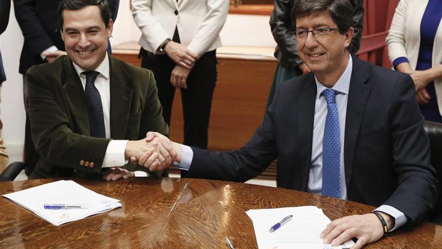El presidente andaluz del PP, Juanma Moreno, y el de Ciudadanos, Juan Marín, estrechan las manos durante la reunión que han tenido esta tarde en el Parlamento andaluz.