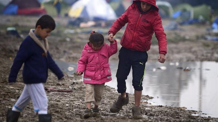 Niños caminan por el barro en un campo de refugiados cerca de Idomeni (Grecia) en la frontera con Macedonia