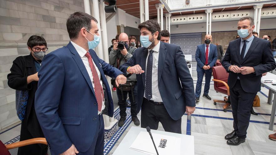 El presidente de la Comunidad de Murcia, Fernando López Miras (c), saluda al portavoz de Vox en el parlamento murciano Juan José Liarte (i) en presencia del portavoz del Partido Popular Joaquín Segado (d). EFE/Marcial Guillén