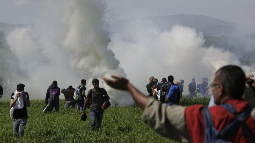 Un grupo de refugiados se enfrentan a los gases lacrimógenos de la policía macedonia en la frontera griega. Amel Emric AP