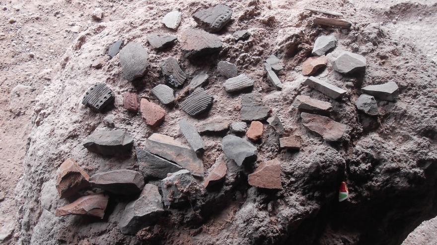 Restos arqueológicos extraídos del expolio y abandonados encima de una piedra en el interior de cueva de Puntagorda.