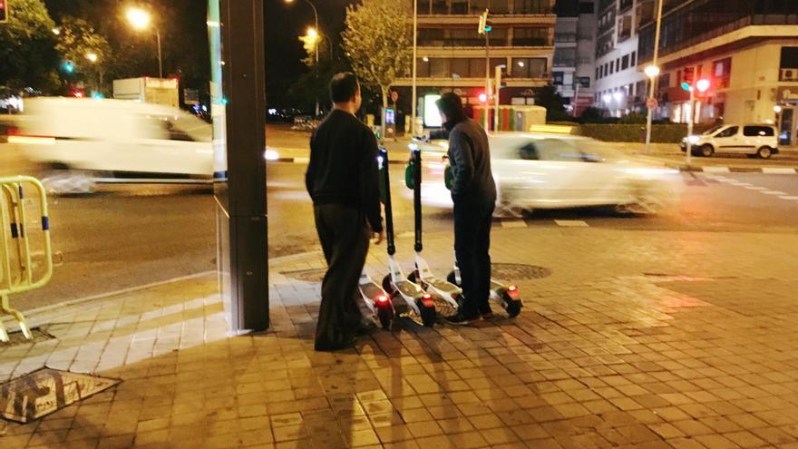 Dos personas recogen patinetes para cargarlos.
