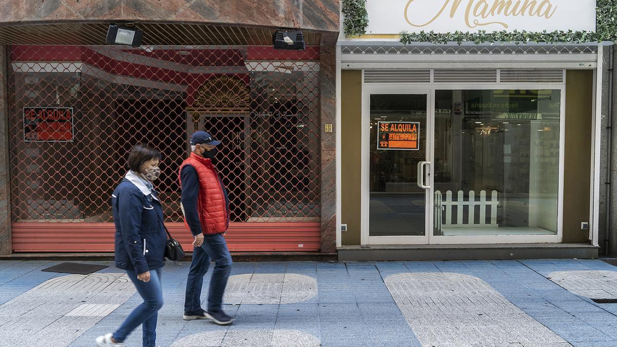 Dos personas pasean por una calle de Santander con varios comercios cerrados.
