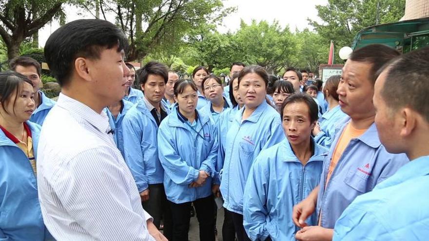 Zhang Zhiru con los trabajadores de una fábrica en huelga