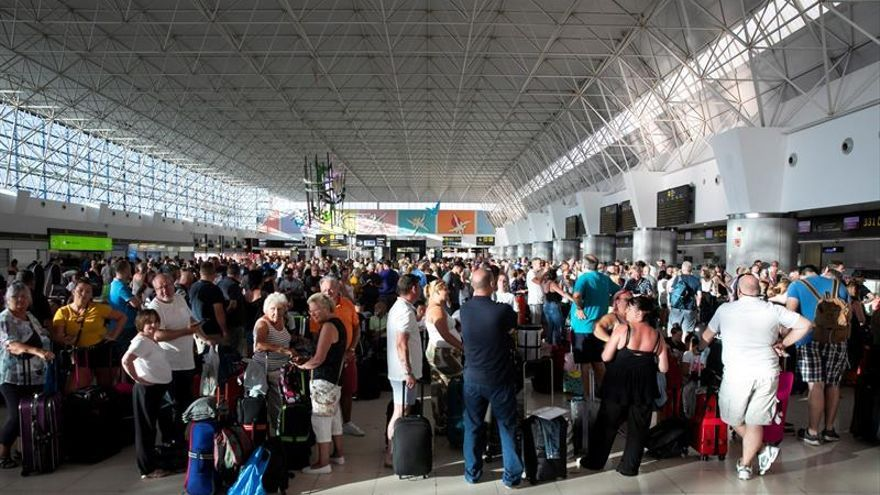Pasajeros de Thomas Cook esperan en el aeropuerto de Gran Canaria, asistidos por personal del Gobierno británico y personal de su embajada en España
