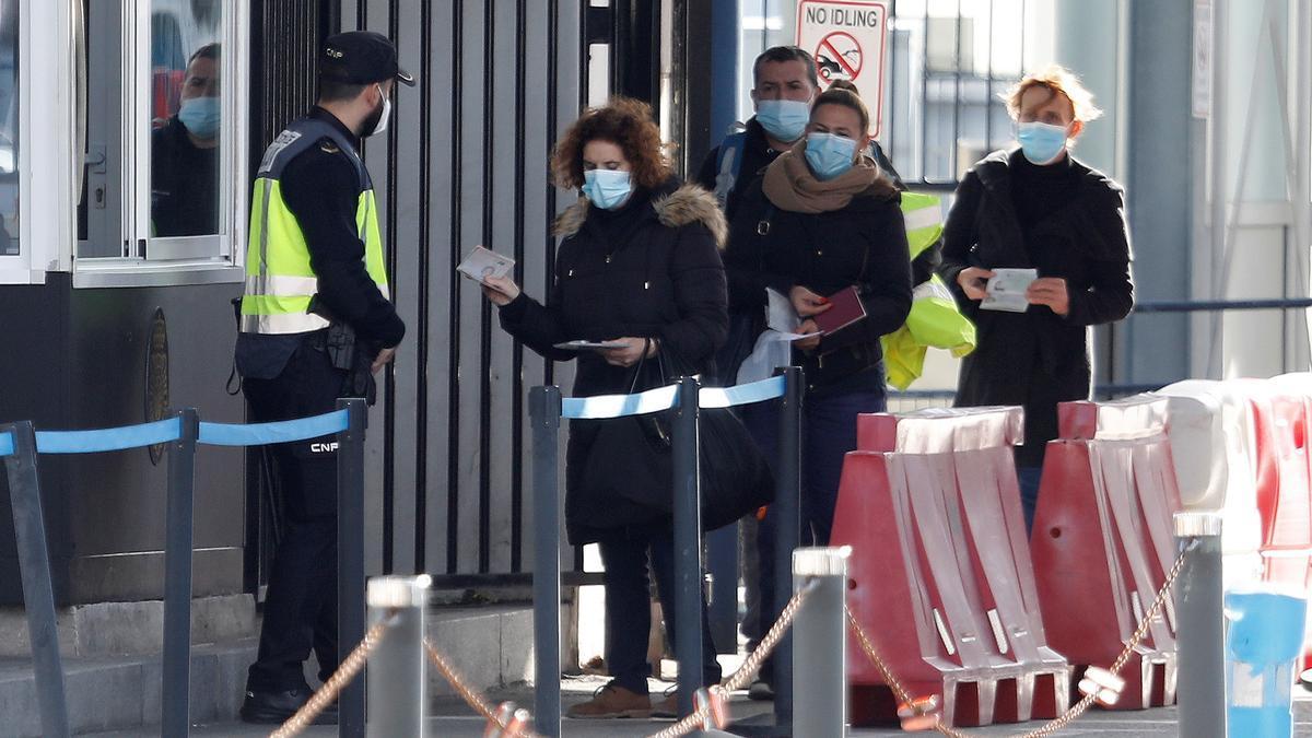 Un grupo de españoles que trabaja en Gibraltar, enseña su pasaporte a la Policía Nacional, para entrar en España.