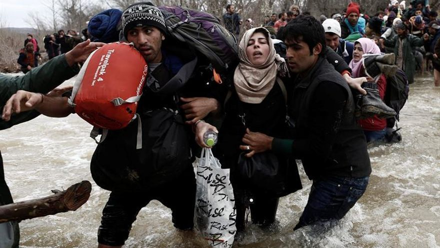 Un grupo de refugiados ayudándose a cruzar un río para pasar la frontera entre Grecia y Macedonia / EFE