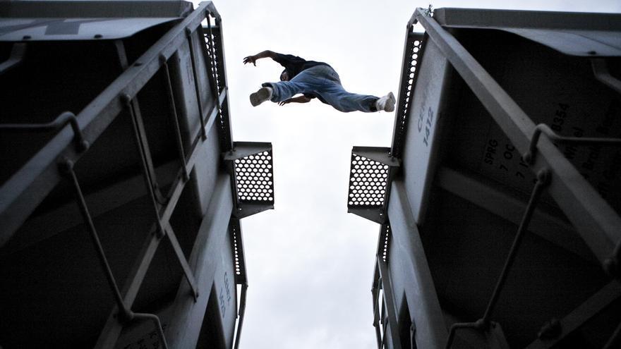 Un migrante saltando de un vagón de un tren de mercancías a otro. FOTO: Edu Ponces / RUIDO Photo.