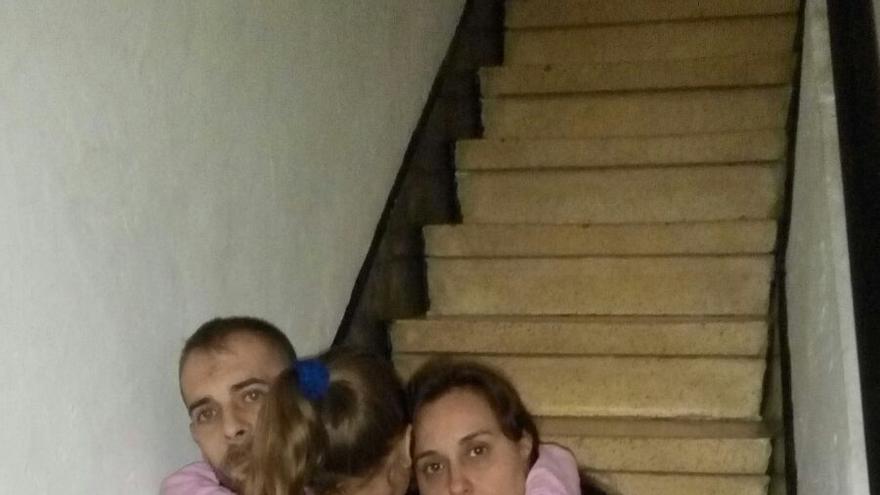 Pilar, junto a su marido, abraza a su hija en las escaleras del edificio en el que residen.