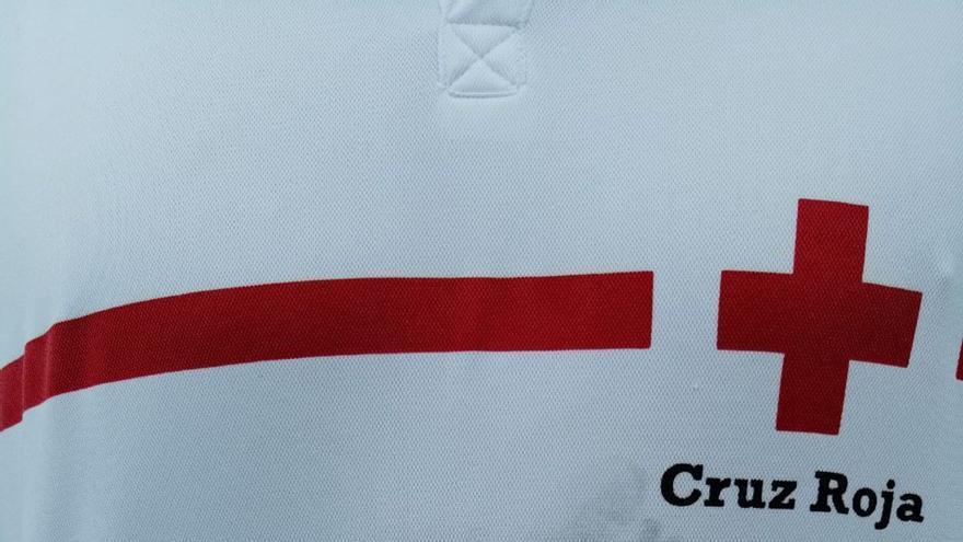 Uno de los bebés rescatados de la patera que llegó a Gran Canaria este viernes deja sus huellas en la camiseta de uno de los voluntarios de Cruz Roja.