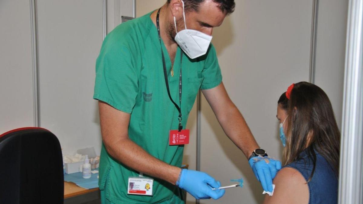 Un sanitario vacuna a una joven contra la COVID-19 en Castellón.