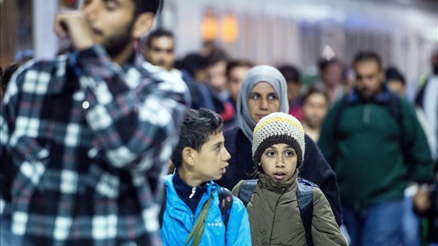Una familia de refugiados en la estación de tren en el aeropuerto de Colonia (Alemania). / Efe.