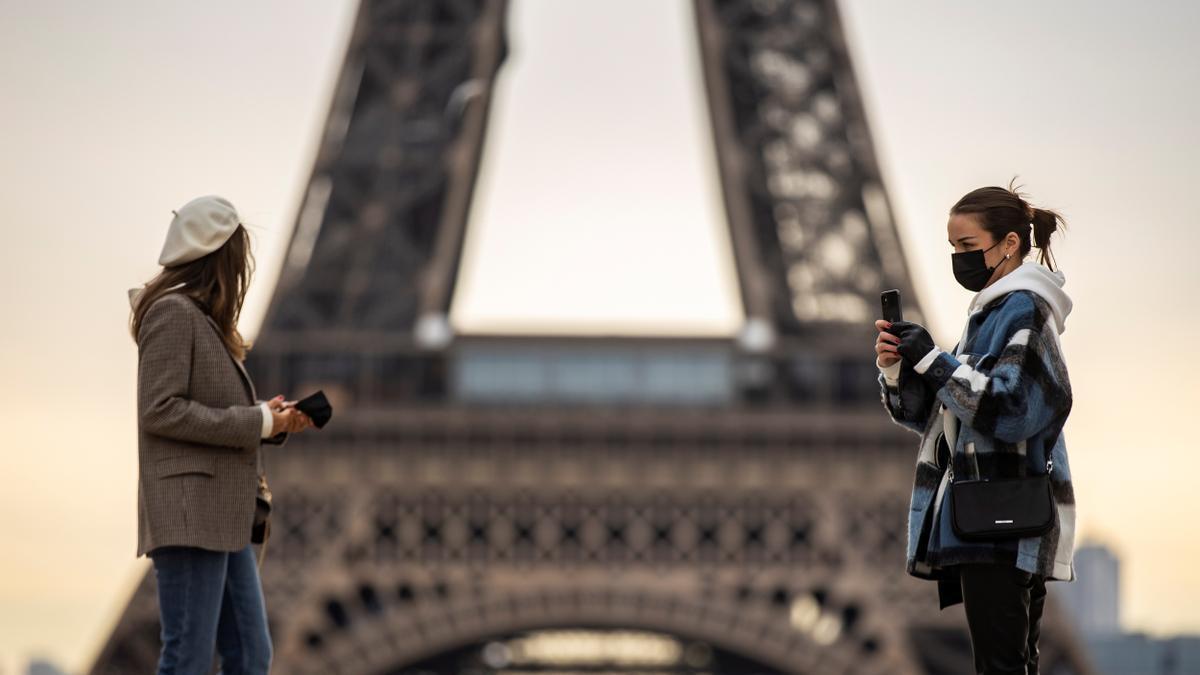 Personas junto a la Torre Eiffel. EFE/EPA/IAN LANGSDON/Archivo