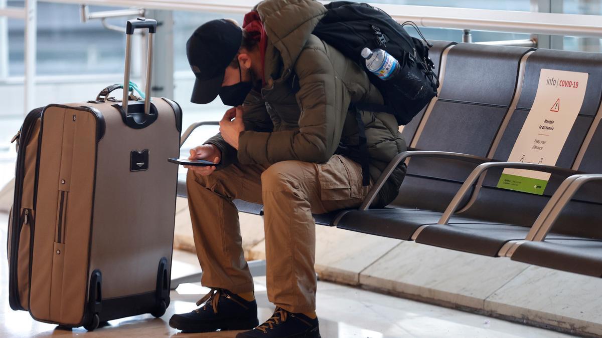 Un viajero revisa su teléfono en el aeropuerto Adolfo Suárez Madrid-Barajas. EFE/Chema Moya/Archivo